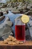 杯苦艾酒用在木桌上的花生 库存照片