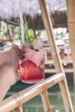 杯草莓汁在人手上在巴厘岛,印度尼西亚一个木咖啡馆  免版税库存图片