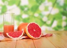 杯葡萄柚汁和切在桌上在围场 库存图片