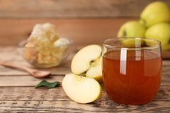 杯蜂蜜和苹果在桌上 免版税库存图片
