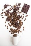 杯被填装的咖啡豆用在白色的巧克力 免版税库存图片