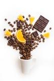 杯被填装的咖啡豆用巧克力和桔子 免版税图库摄影