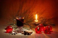 杯被仔细考虑的酒、蜡烛和圣诞节球 库存图片