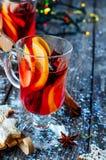杯被仔细考虑的酒用桔子、曲奇饼和有气味的肉桂条 免版税库存图片