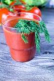 杯西红柿汁和新鲜的蕃茄在老木桌上 库存图片
