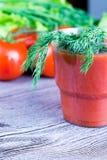 杯西红柿汁和新鲜的蕃茄在老木桌上 免版税库存照片