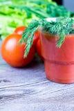 杯西红柿汁和新鲜的蕃茄在老木桌上 图库摄影