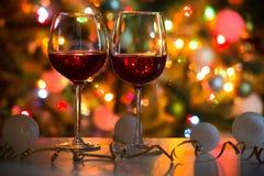 杯酒和圣诞节球在圣诞灯背景  库存照片