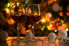 杯酒和圣诞节球在圣诞灯背景  图库摄影