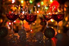 杯酒和圣诞节球在圣诞灯背景  库存图片