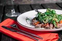 杯酒和沙拉用温暖的小牛肉 图库摄影