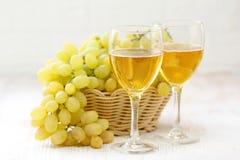 杯酒和葡萄在篮子在一张木桌上 库存照片