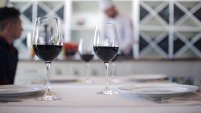 杯酒在餐馆的桌上,厨师的背景的准备面团 股票录像