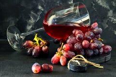 杯酒用在一个黑木立场的葡萄 免版税库存照片