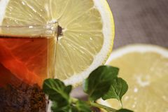 杯酿造的红茶用一个黄色柠檬和绿色薄菏 免版税库存照片