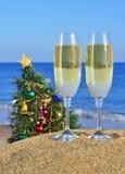 杯香槟和在海滩的圣诞树 免版税图库摄影