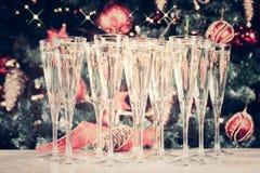 杯香槟有圣诞树背景和闪闪发光 免版税库存照片