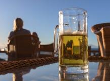 杯鲜美冰镇啤酒,站立在海滩酒吧的桌上 免版税库存照片
