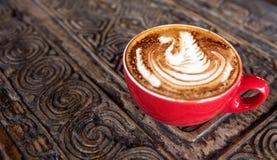 杯鲜美热奶咖啡在红色c的木织地不很细桌上 库存照片