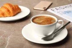 杯鲜美芳香咖啡和新月形面包早餐 免版税库存照片