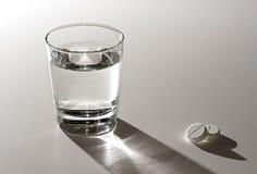杯水和阿斯匹灵。 库存图片