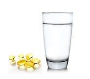 杯水和鱼油在白色背景 免版税库存图片
