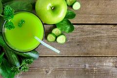 杯绿色蔬菜汁,在土气木头的向下看法 库存图片