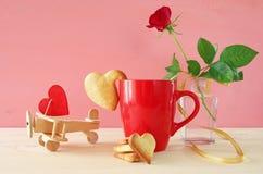 杯coffe用在一朵红色玫瑰旁边的曲奇饼在花瓶 库存图片