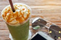 杯matcha greentea frappe用焦糖鞭打了在棕色吠声美好的纹理背景的奶油与温暖的光 免版税库存图片