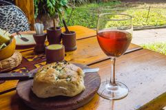 杯rosé酒用在一个木板的面包 免版税库存照片