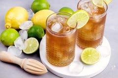 杯Tsasty与冰块的冰茶和柑橘冷的Summ唔饮料木剥削者和未加工的柠檬和石灰在背景 免版税库存图片