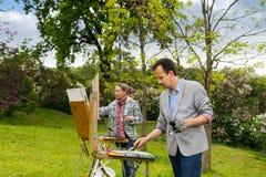 绘杰作的两位中年梦想的艺术家 库存照片