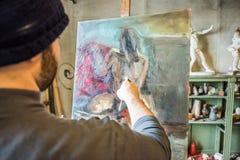 绘杰作的艺术家在他的演播室-接近的射击 免版税库存图片
