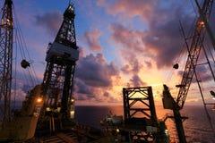 杰克在太阳日出时间的石油钻井船具 库存照片
