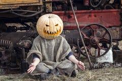 杰克灯笼用在他的头的一个南瓜在拖拉机附近思考 免版税库存照片