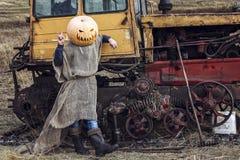杰克灯笼用在他的站立在拖拉机附近的头的一个南瓜 免版税库存图片