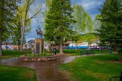 杰克逊HOLE,怀俄明,美国- 2018年5月23日:的游人走在接近牛仔一个古铜色雕象的一个公园的室外观点  图库摄影