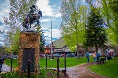 杰克逊HOLE,怀俄明,美国- 2018年5月23日:的游人走在接近牛仔一个古铜色雕象的一个公园的室外观点  免版税库存图片
