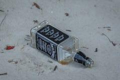 杰克Daniels瓶空在沙子 库存图片