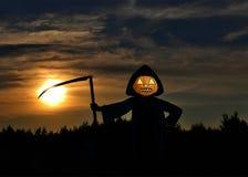 杰克o灯笼在一个黑斗篷和有铁大镰刀的反对 免版税库存照片