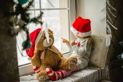 松劲在冬天窗口圣诞节的愉快的儿童女孩 库存照片