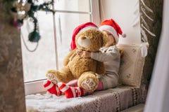 松劲在冬天窗口圣诞节的愉快的儿童女孩 免版税图库摄影