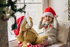 松劲在冬天窗口圣诞节的愉快的儿童女孩 免版税库存照片