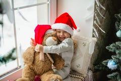 松劲在冬天窗口圣诞节的愉快的儿童女孩 免版税库存图片