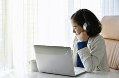 轻松和愉快的在耳机的女实业家听的音乐 免版税库存照片