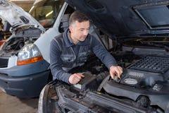 松开在汽车修理的技工油箱 免版税库存图片