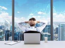 松弛商人的背面图用在他的头后的横渡的手,看NYC 免版税库存图片
