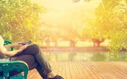 松弛妇女坐长凳使用在日落的手机 免版税库存照片