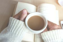 松弛片刻、葡萄酒口气的咖啡和一本书在木桌上在自然背景中,颜色和软的焦点 库存照片