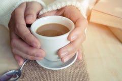 松弛片刻、葡萄酒口气的咖啡和一本书在木桌上在自然背景中,颜色和软的焦点 图库摄影